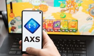 Russia Moscow 30.05.2021.Logo,screenshot of blockchain nft ethereum cryptocurrency game Axie in laptop,mobile phone.Man playing,collecting,creating crypto pet,heroes. Earning digital money tokens AXS.