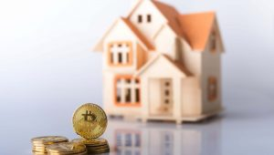 Concept for purchasing real estate with Bitcoins or comparison of prices of both investments - pile of golden colored Bitcoin coins in sharp focus in front of blurred model house on white background